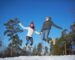 Joyful young couple jumping in winter park or forest