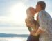 Beautiful kissing couple in romantic embrace on beach at a sunny day. Summer time flirt outdoor.